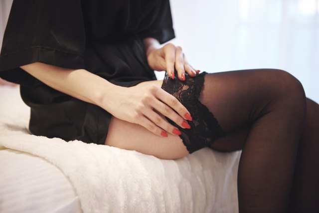 Cropped view of woman sitting on bed putting on stocking
