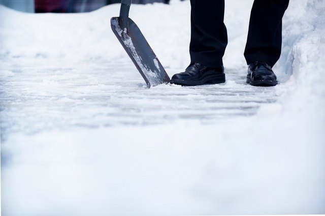Welldressed man with snow shovel and copyspace