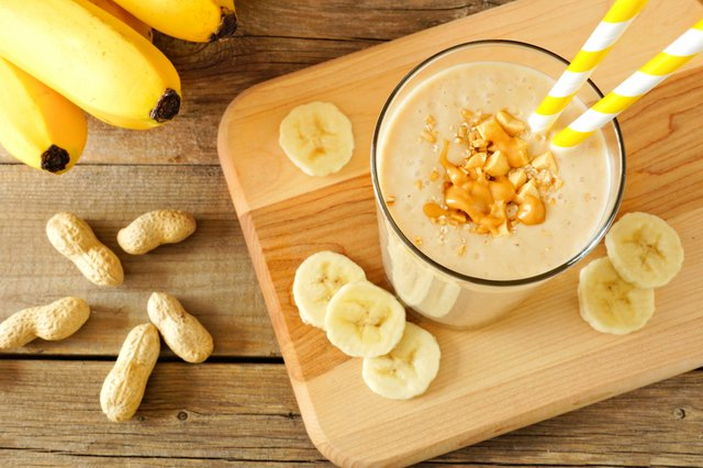 Peanut-butter banana oat smoothie with straws, on wood