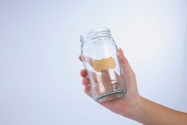 Hand Holding Glass Jar With Blank Label Against White Background