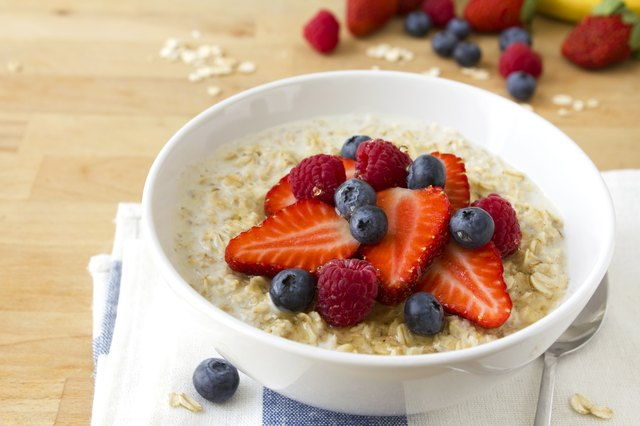 A bowl of oatmeal with blue berries and strawberries