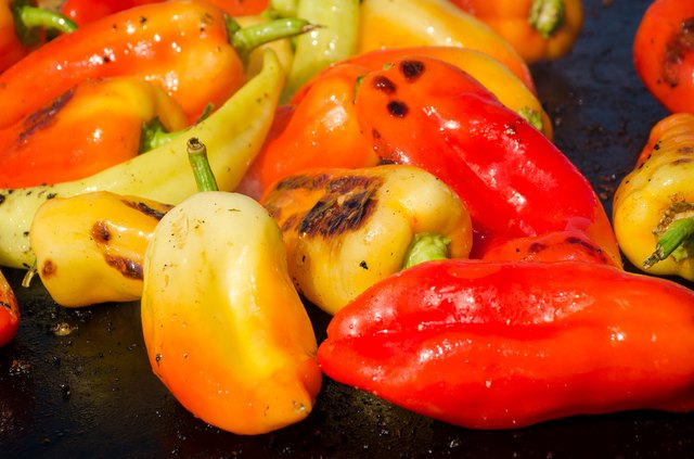 Red,green,yellow peppers on a grill