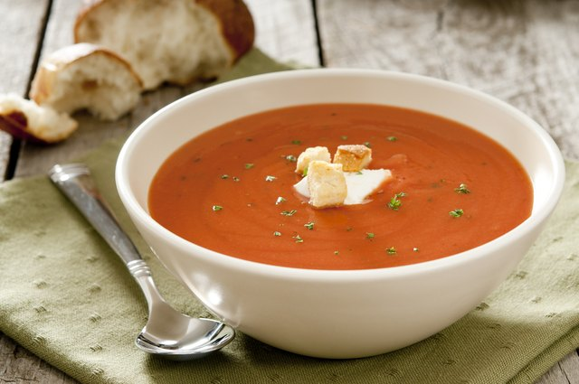 Tomato soup in a white bowl with spoon