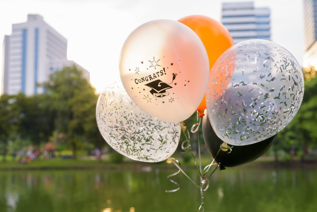 Bunch of decorative balloons for graduation against view of Lumpini Park in Bangkok Thailand