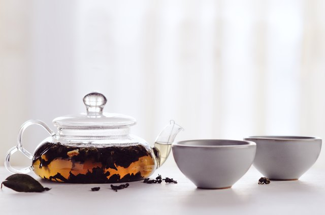 Black tea brewed in a transparent teapot with small cups on a white table. Concept tea ceremony, Chinese tradition, healthy drink