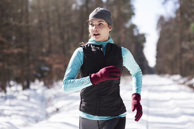 Portrait of young woman jogging in winter forest