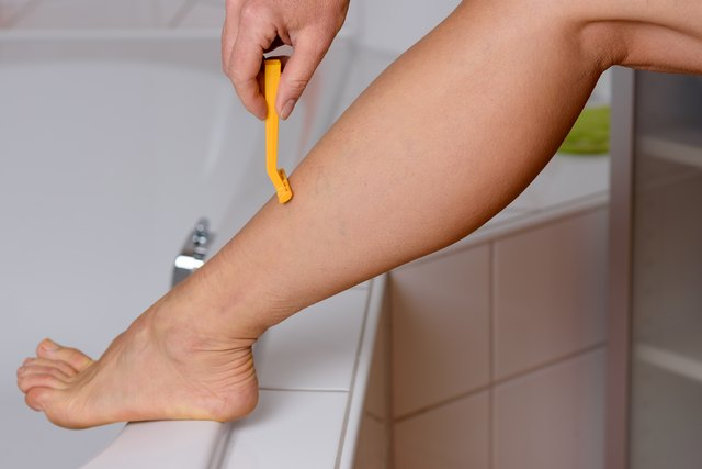 Low Section Of Woman Using Yellow Razor On Leg In Bathroom