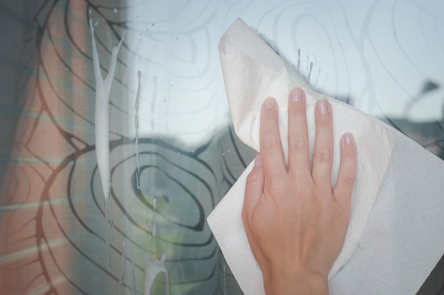Cropped Hand Of Woman Cleaning Glass Window With Textile At Home