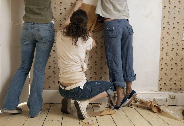 Three friends tearing down wallpaper