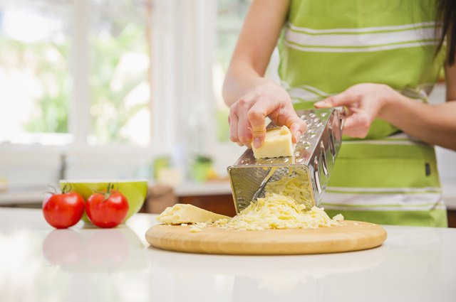 Hispanic woman grating cheese in domestic kitchen