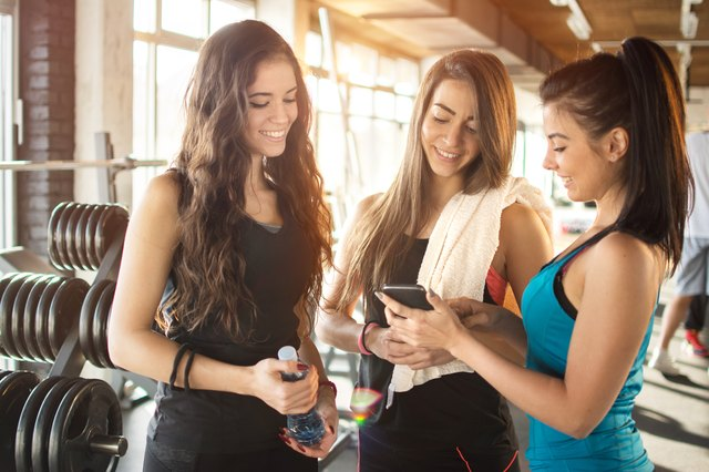 Three young women looking at smartphone and talking in gym,