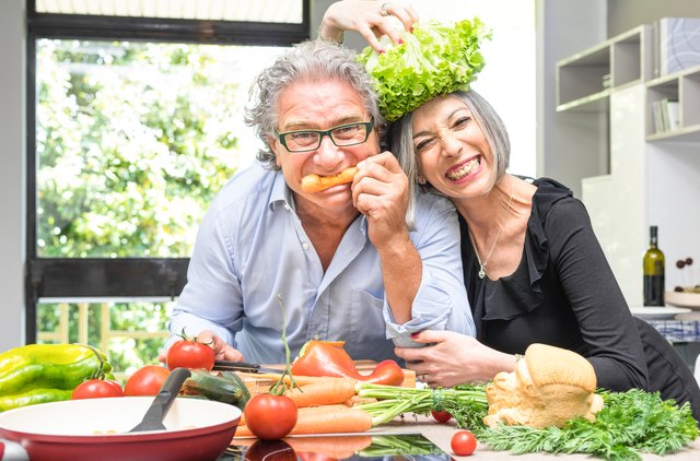Senior couple having fun in kitchen cooking healthy food together