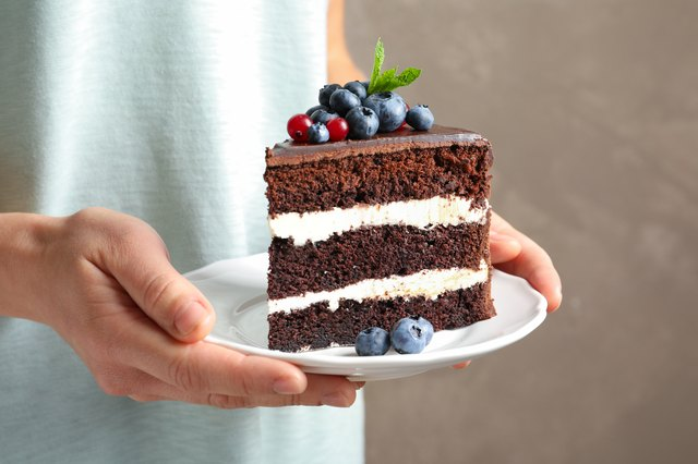 Woman holding plate with slice of chocolate sponge berry cake on grey background, closeup