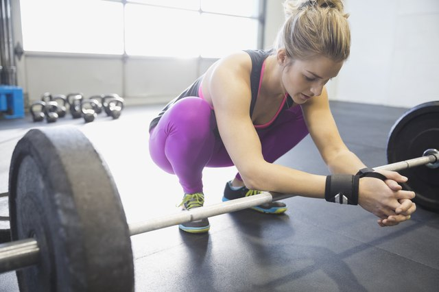 Woman leaning on barbell