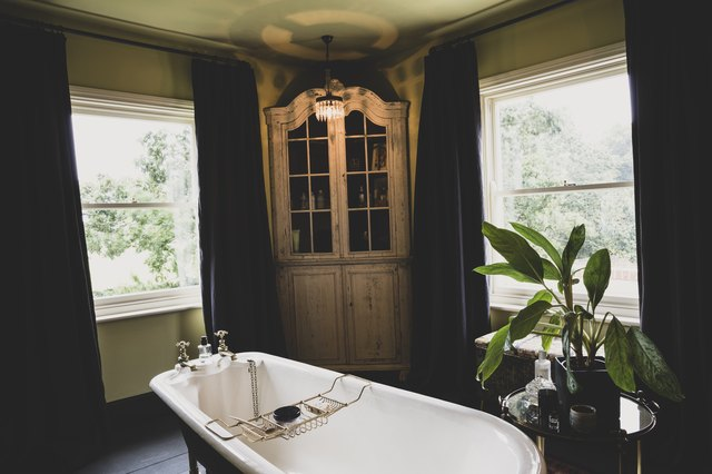 Interior view of bathroom with wooden corner cabinet  between sash windows, roll top bath with brass bath caddy.