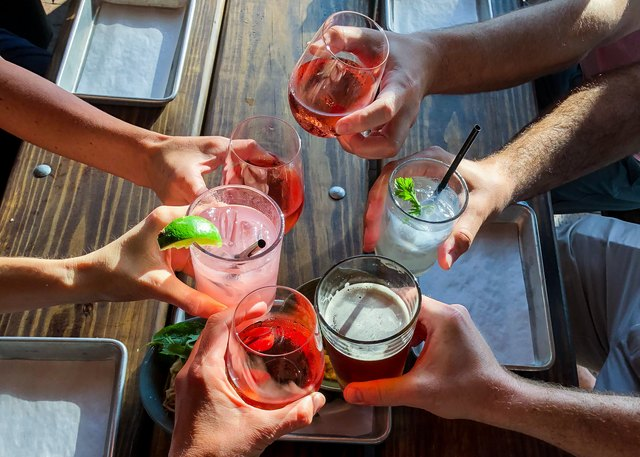 Overhead view of six people making a celebratory toast