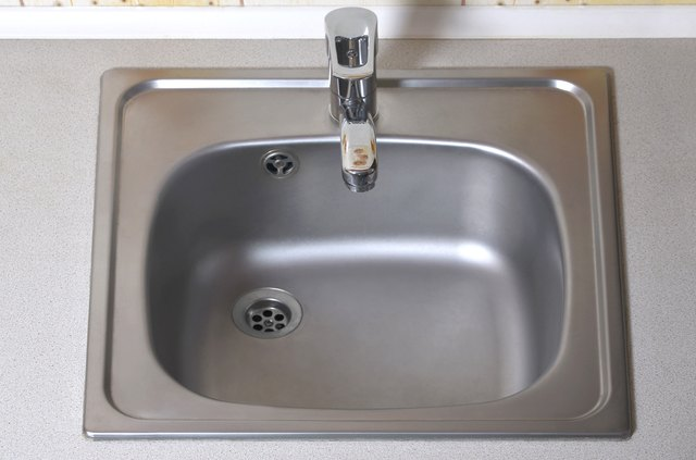 Sink with silver faucet. New equipment in kitchen counter