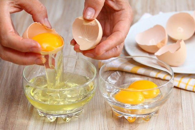 Woman hands breaking egg to separate  egg-white and  yolk
