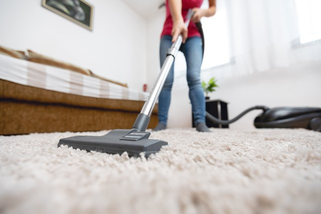 Young woman vacuuming house