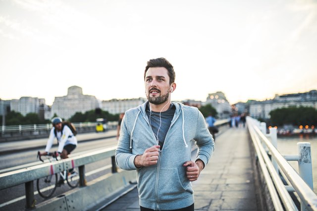 Young sporty man with earphones running on the bridge outside in a city.
