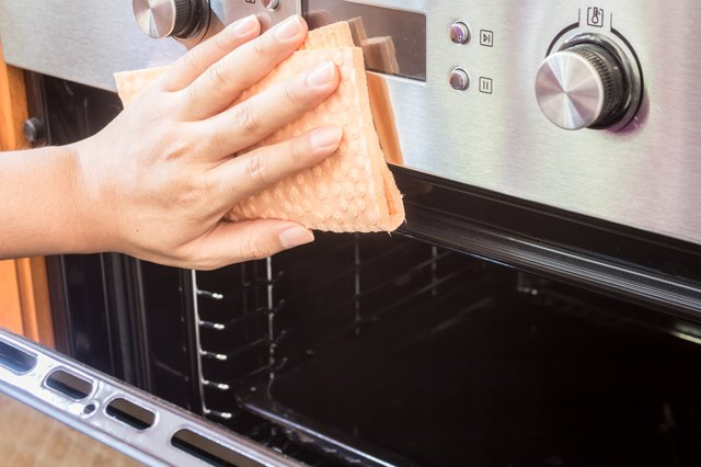 Cropped Hands Of Woman Cleaning Oven At Home