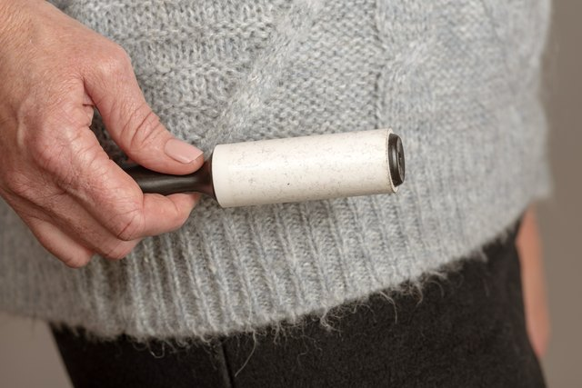 Woman's hand holding a adhesive roller brush to collect hair and fluff from a sweater
