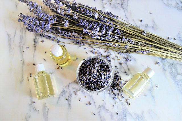 Aromatic oils with lavender flowers on marble background