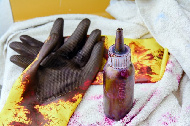 Bottle of hair dye and stained rubber gloves on a bathroom counter.