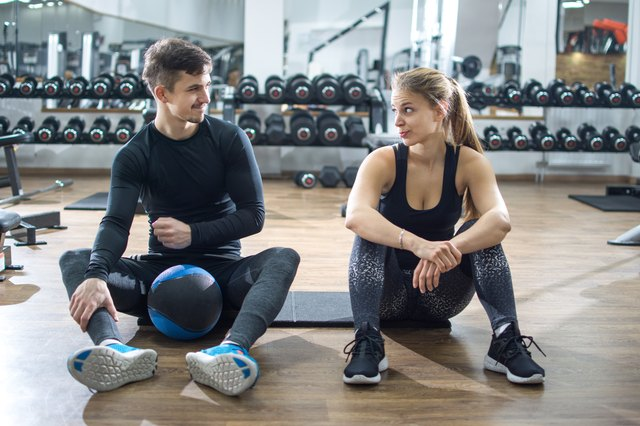 Sporty couple talking during exercise break in gym