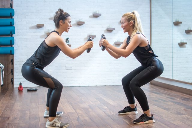 Two women in sports wear squatting with weights together in fitness center.