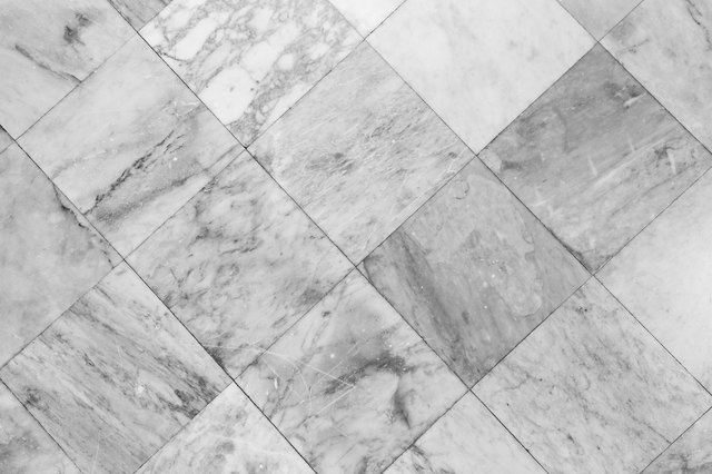 Close-up of a smooth marble floor viewed from above in black and white.