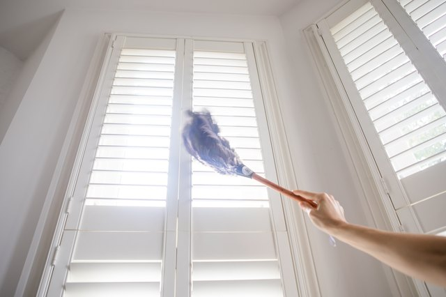 Cleaning the shutters with a feather duster
