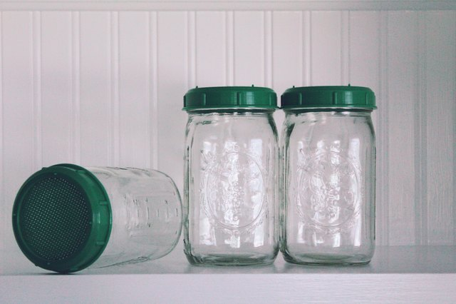 Mason jars with green lids on a shelf