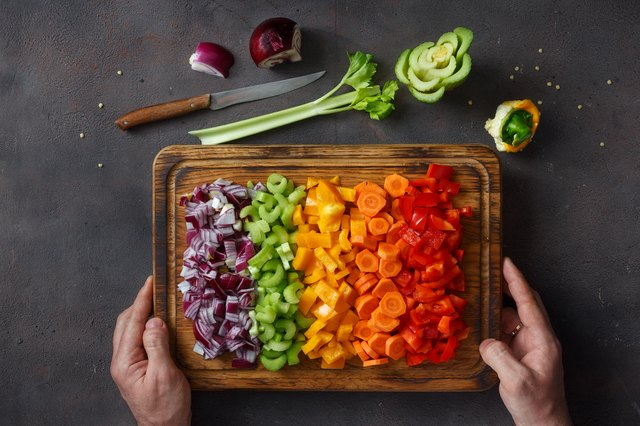 Male hands holding cutting board with sliced fresh vegetables