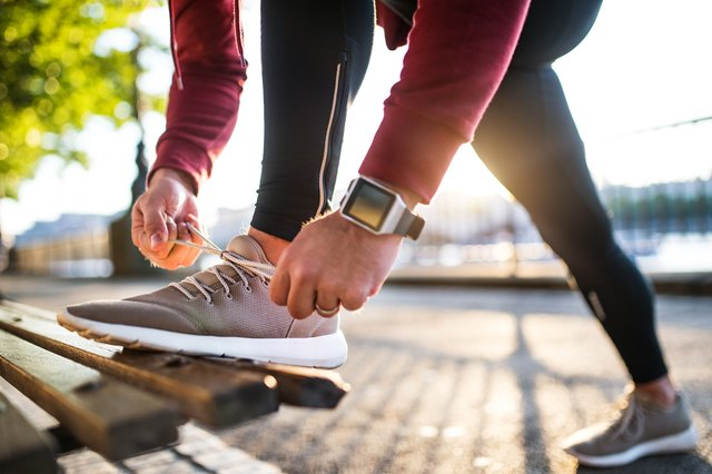 Young sporty man with smart watch tying shoelaces on a bench outside in a city at sunset.
