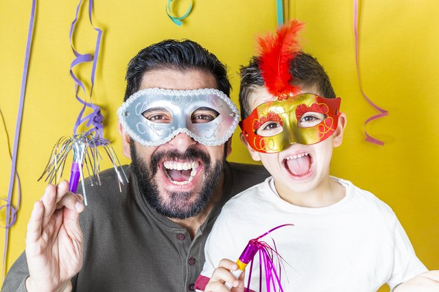 Father and son celebrating Carnival with masks