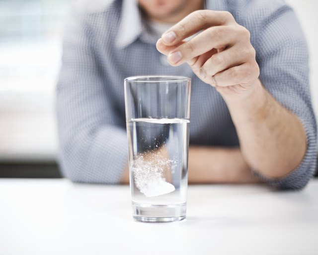 Man dropping antacid into a glass of water