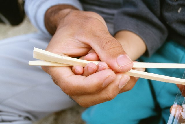 Close-up of a father teaching his son the use of chopsticks, Okinawa, Japan