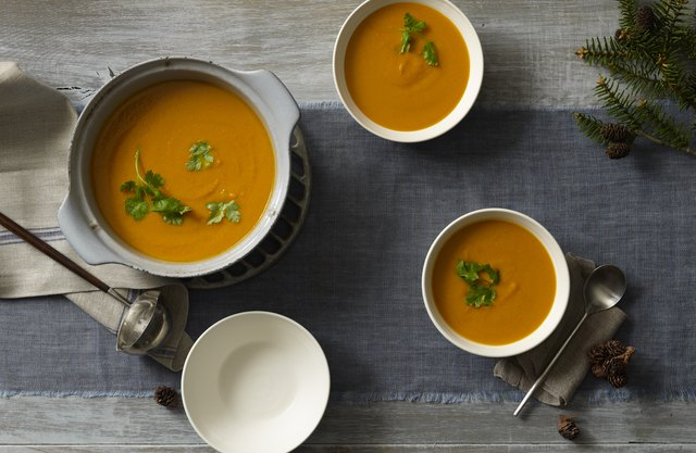 A table filled with bowls of butternut squash soup.