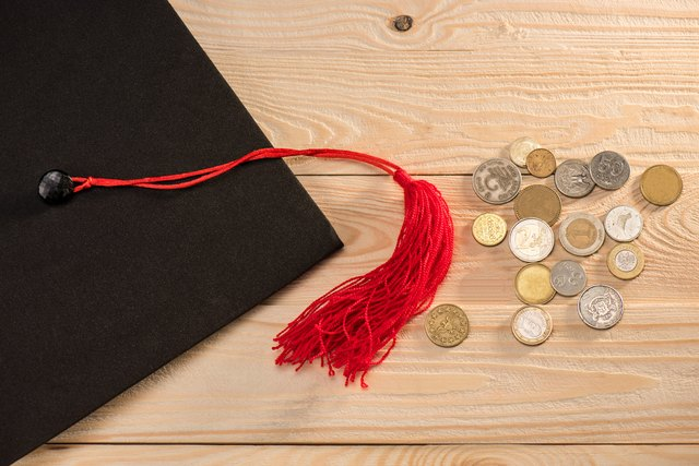 Close-up top view of graduation mortarboard and coins on wooden table, education concept