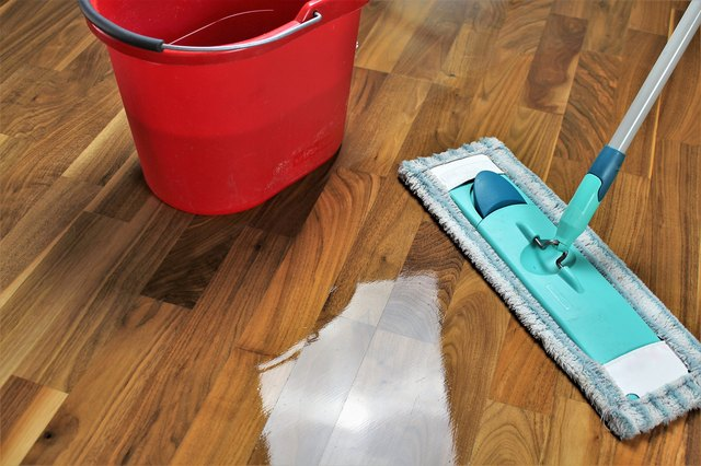 High Angle View Of Cleaning Equipments On Hardwood Floor