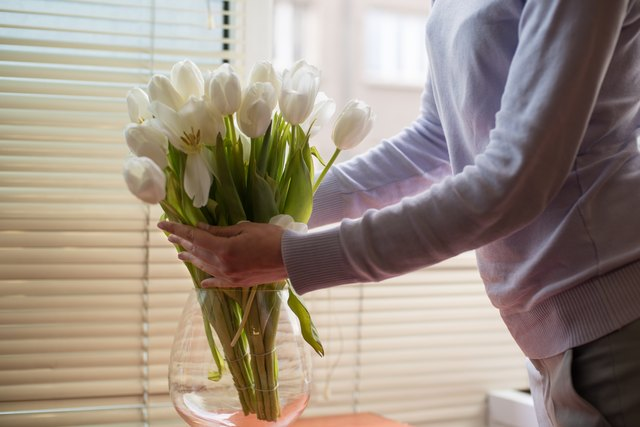 Woman arranging tulips in a vase