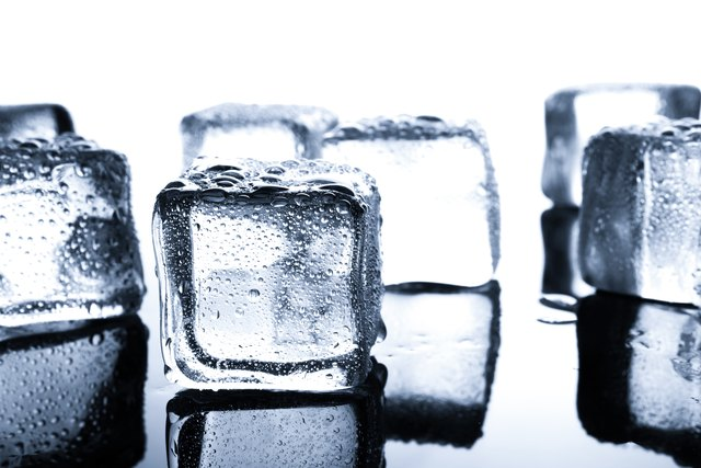 Close-Up Of Ice Cubes On Table Against White Background