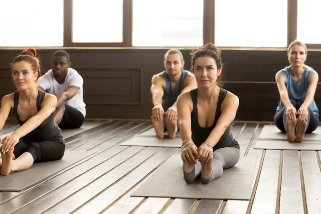 Group of sporty people in paschimottanasana exercise