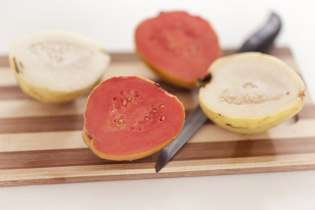 White and red guava fruit on cutting board