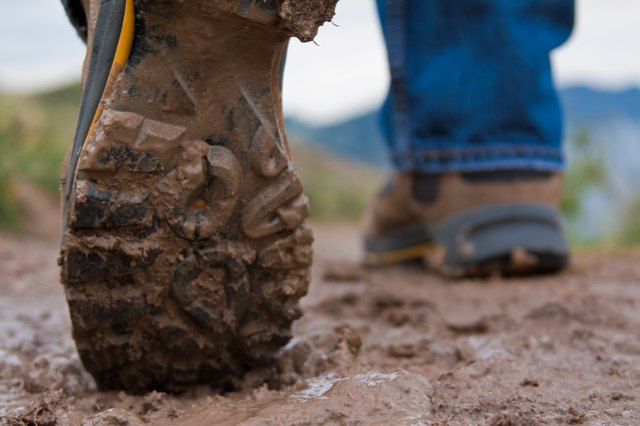 A pair of muddy hiking boots in the mud