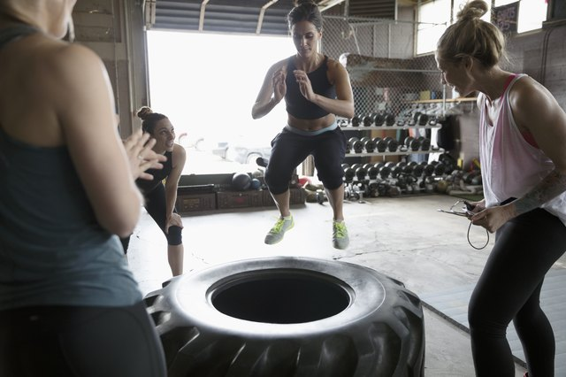 Women cheering classmate jumping on large tire in gym exercise class in gritty gym