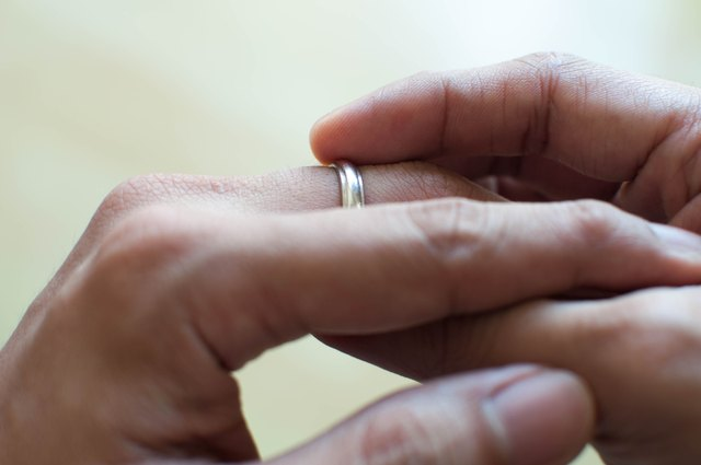 A man is holding his wedding ring