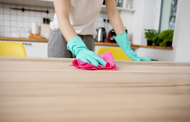 Midsection Of Young Woman Cleaning Wooden Table At Home