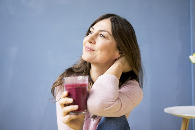 Smiling woman holding glass of juice
